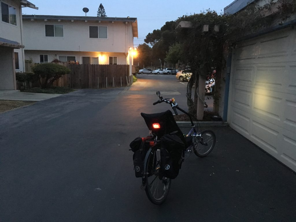a recumbent bicycle shows its front and back lights in a dim driveway