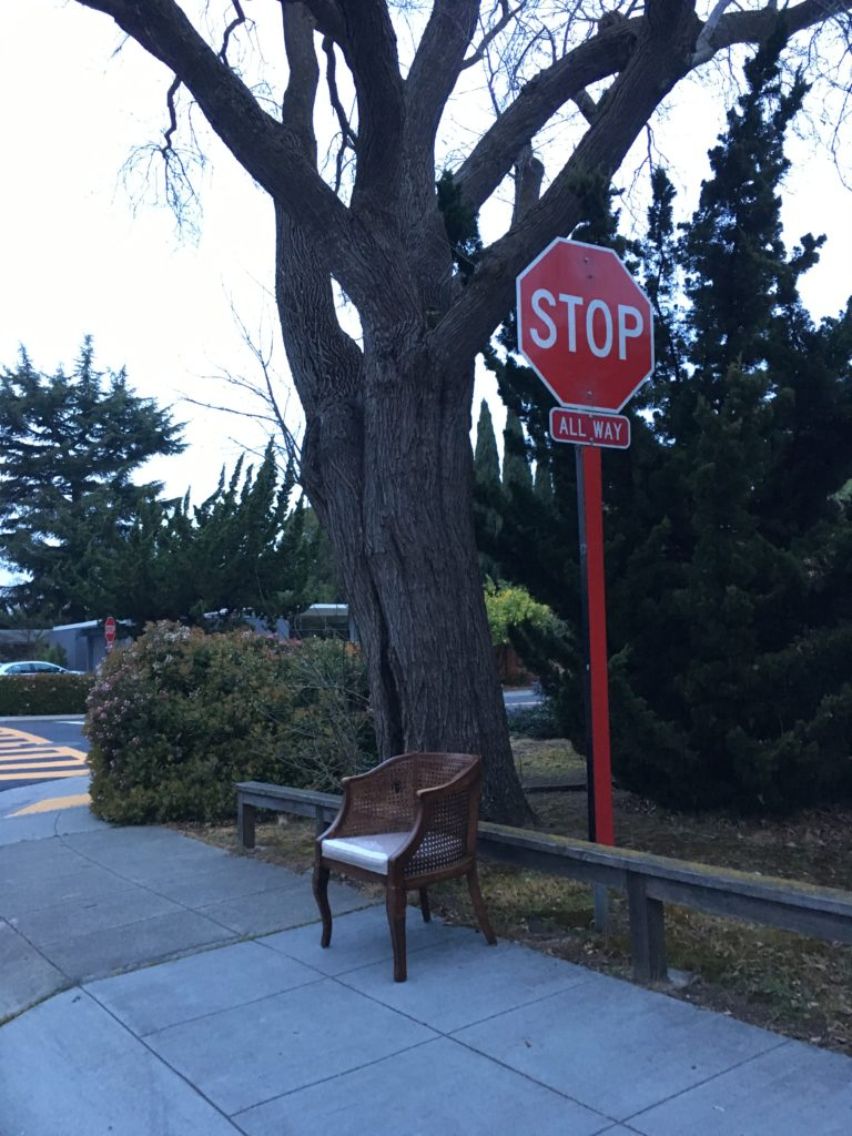 a broken arm chair is sitting on the sidewalk next to a stop sign