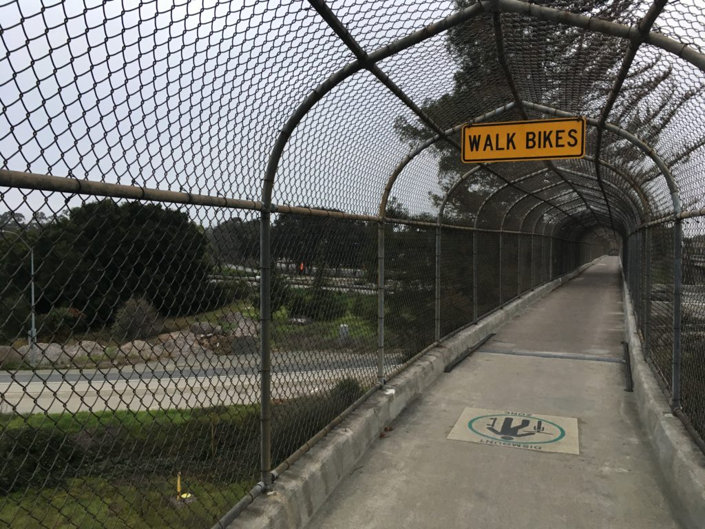 "a chainlink-covered bike bridge over a freeway with a sign that says ""walk bikes"""