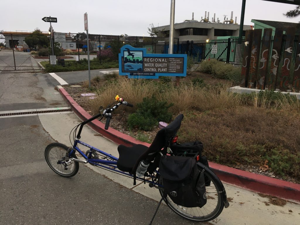 a recumbent bicycle posed in front of the buildings for a water treatment plant