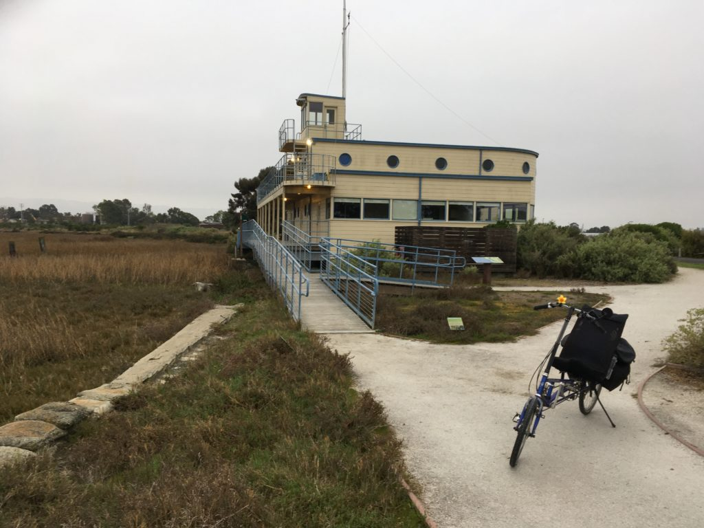 a building that looks almost like a ship sits near a marsh that used to be a yacht harbor