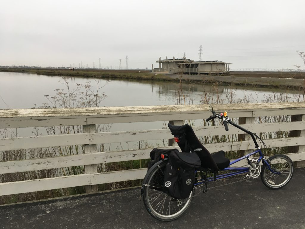 a recumbent bicycle by the railing of a bridge. a body of water flows beneath the bridge. a building on stilts, the baylands nature center, sits on a levee across the way.