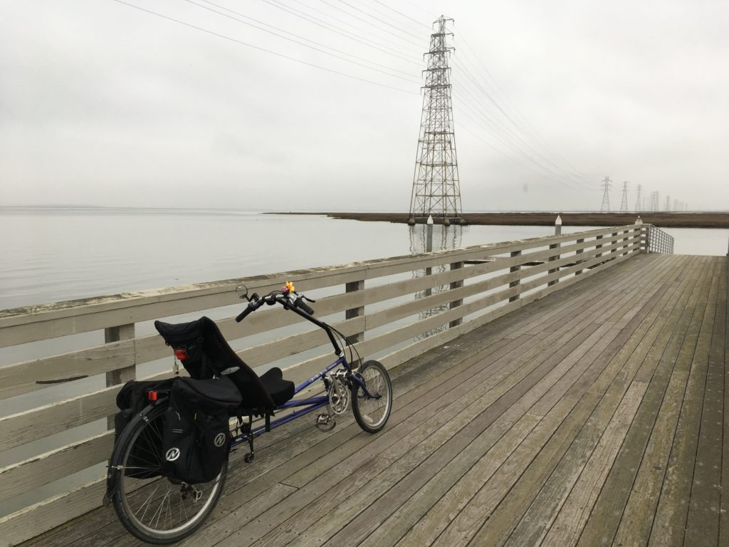 a recumbent bicycle is posed agains the railing of a dock near the open water of San Francisco Bay
