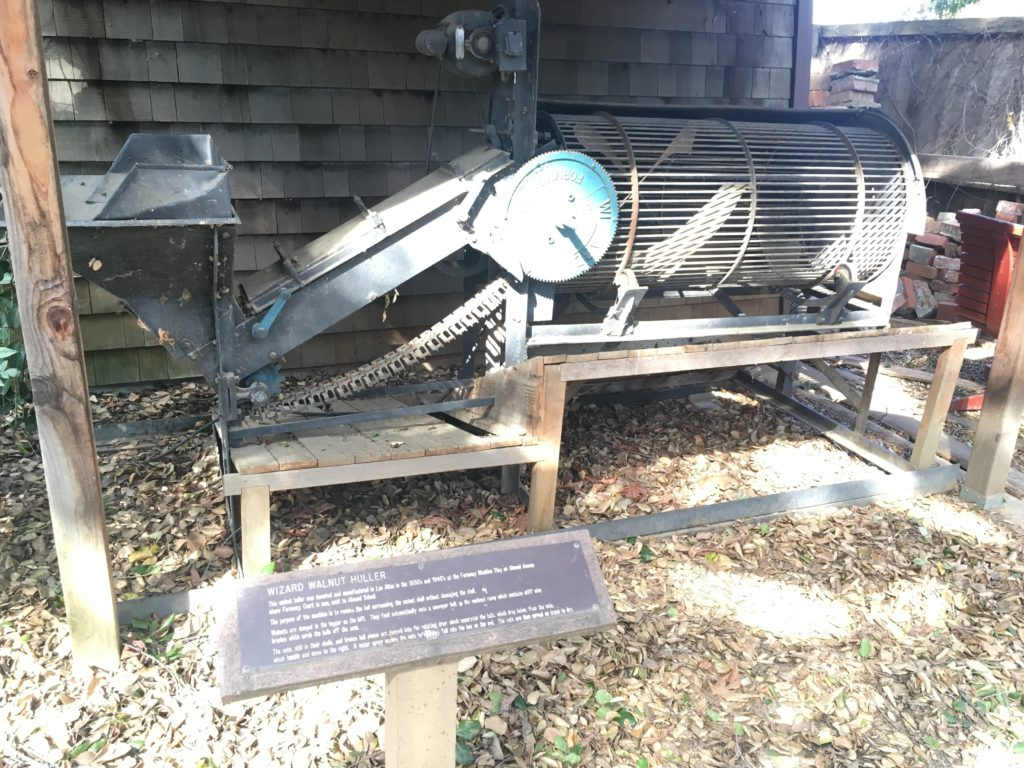 an antique walnut huller machine and explanatory sign