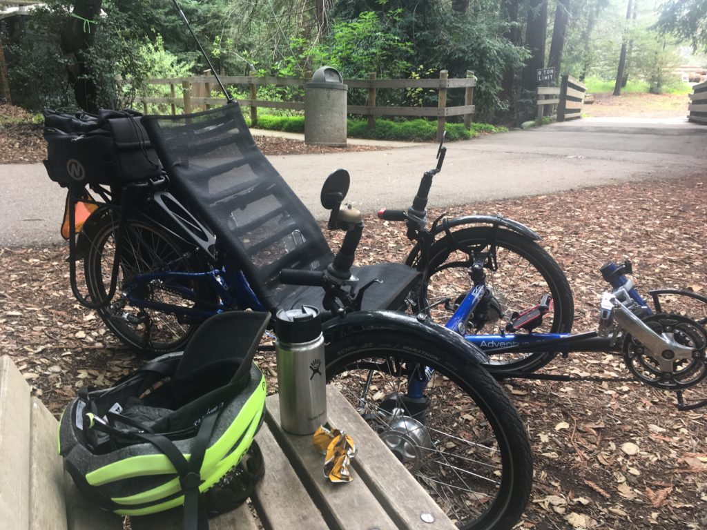 a recumbent trike, a bike helmet, a thermos of hot tea and a bench in a park