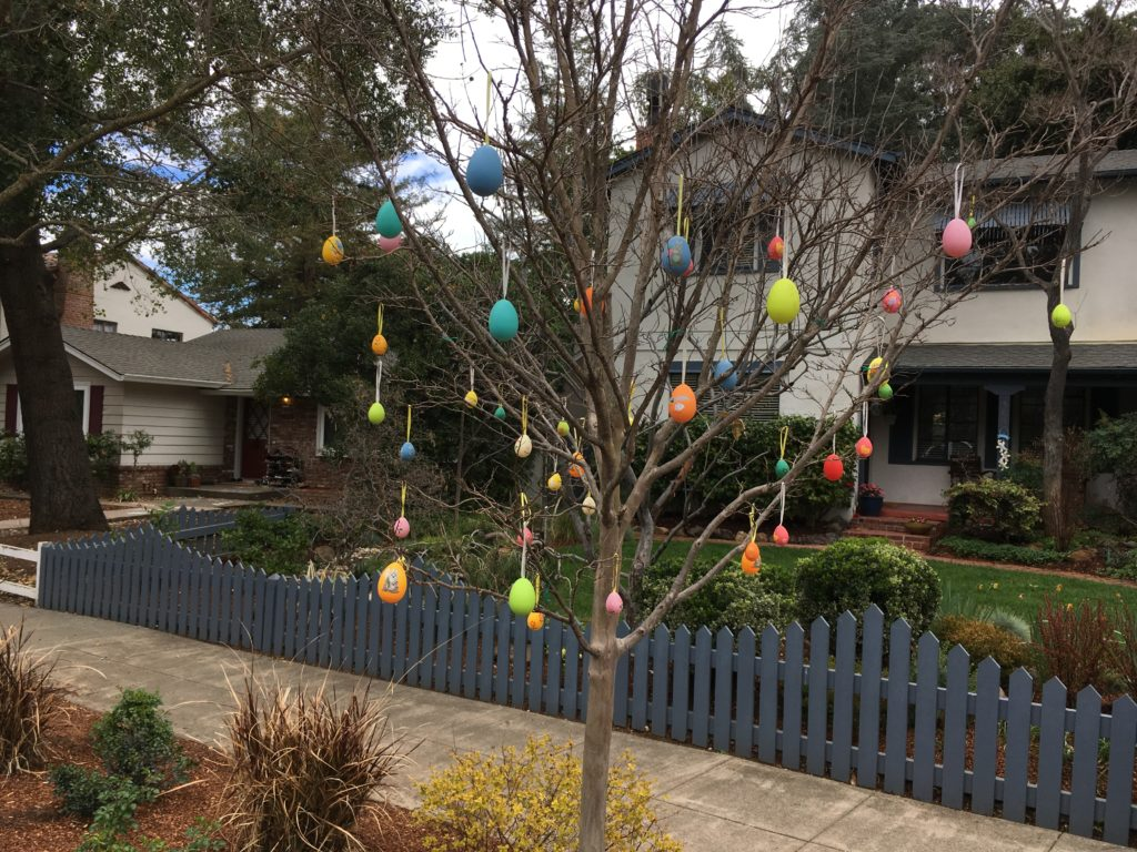 a small tree in front of a house with many brightly colored easter eggs hanging from the branches