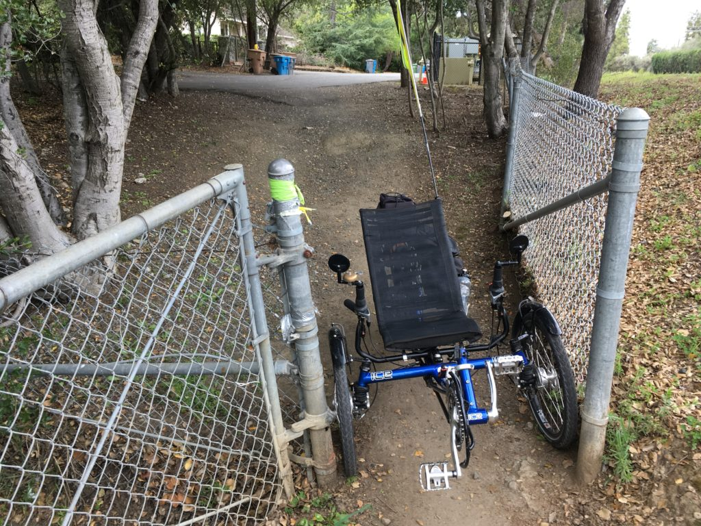 recumbent trike at an almost too-small opening on an informal path between streets