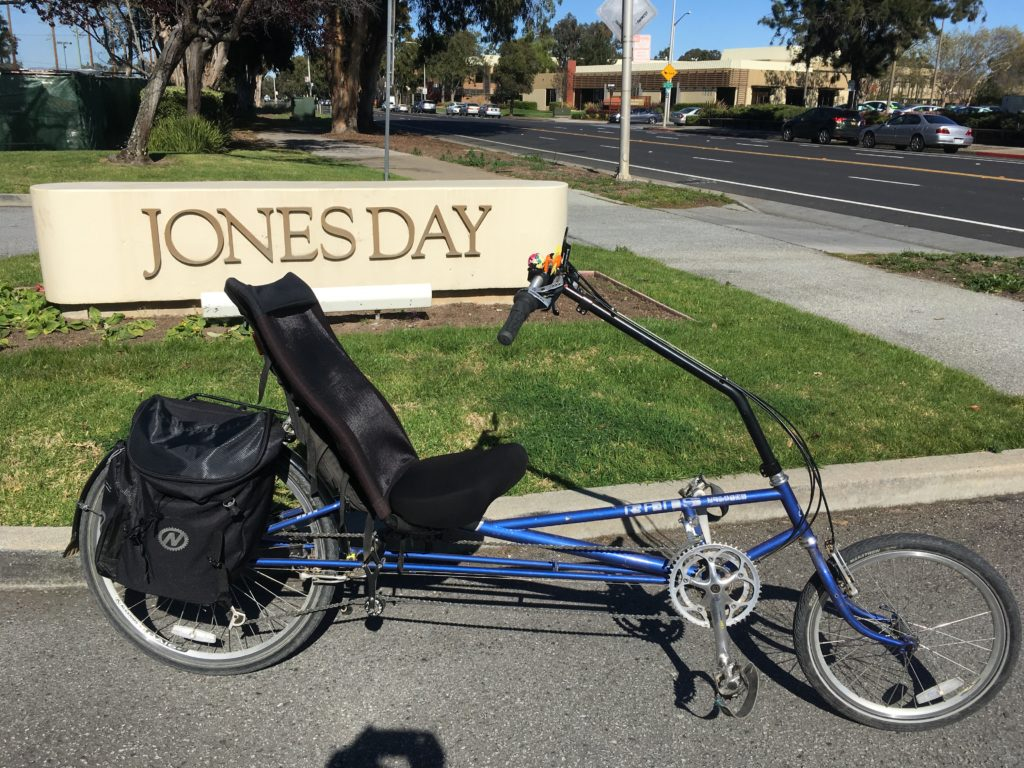 a recumbent bicycle in front of a business sign that says Jones Day
