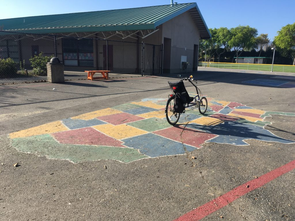a bicycle is posed in the middle of a map of the united states that is painted on the playground of an elementary school