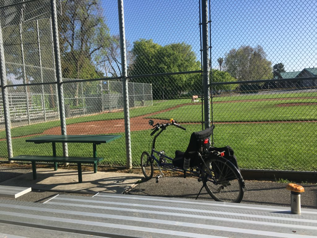 a view of a baseball diamond from the bleachers, with bicycle posed near the bleachers