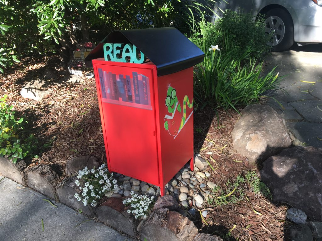 "a little free library that says ""Read"" on it and has a decal of a book worm character"