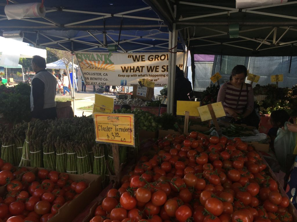 a stall at a farmer's market with many different types of vegetables, including tomates
