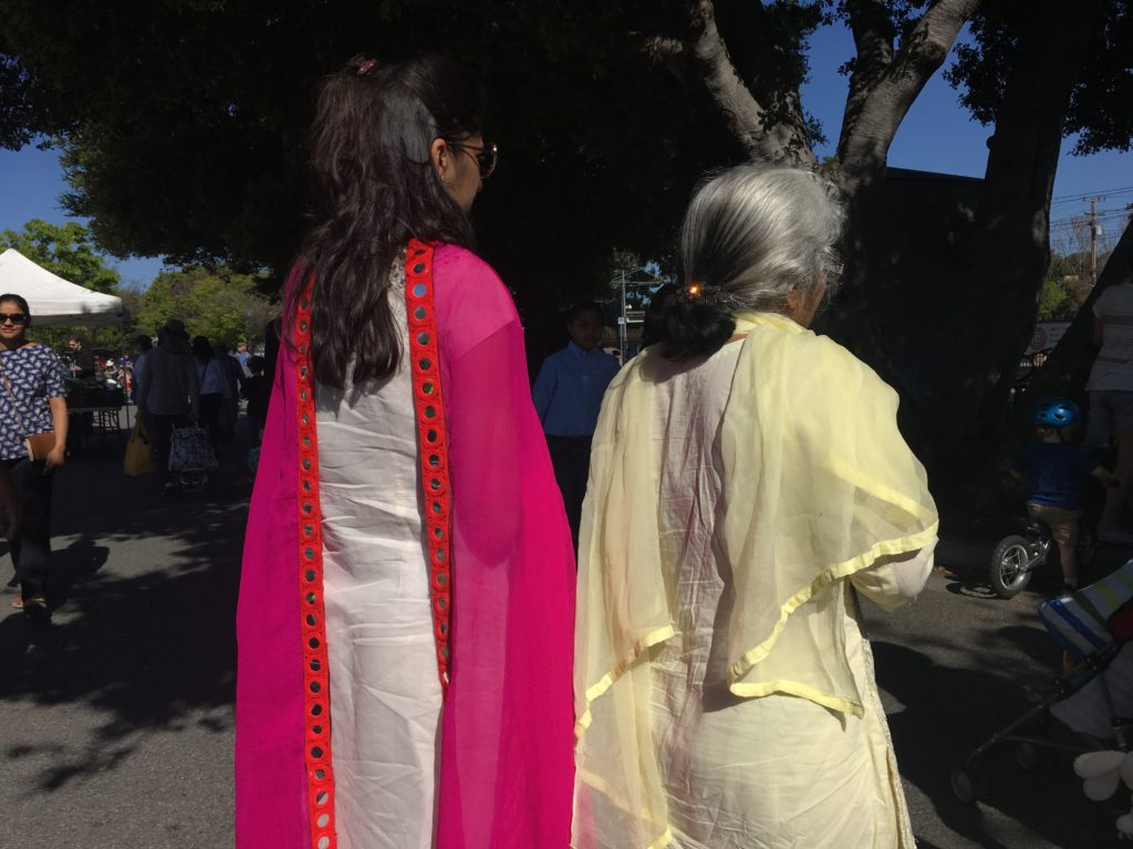 Two women wearing colorful saris attending a farmer's market.