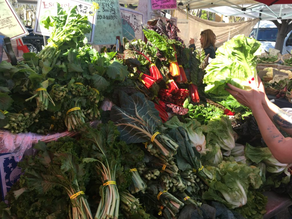 Stacks of chard at a farmer's market stall.