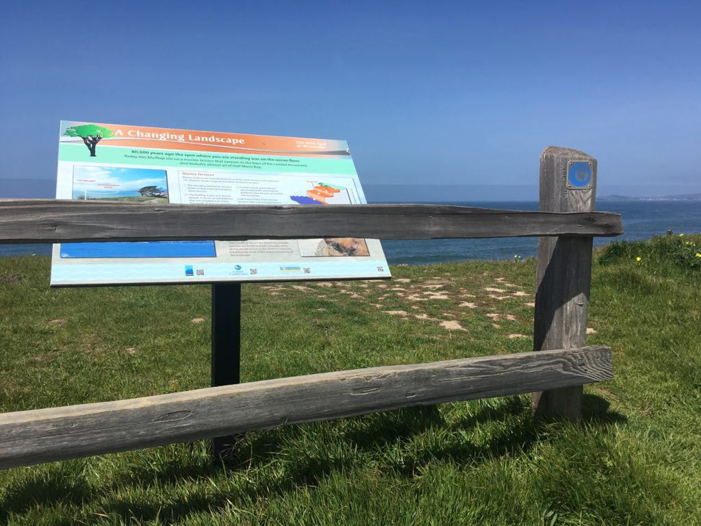 an interpretive panel and a short fence overlooking the ocean near Half Moon Bay