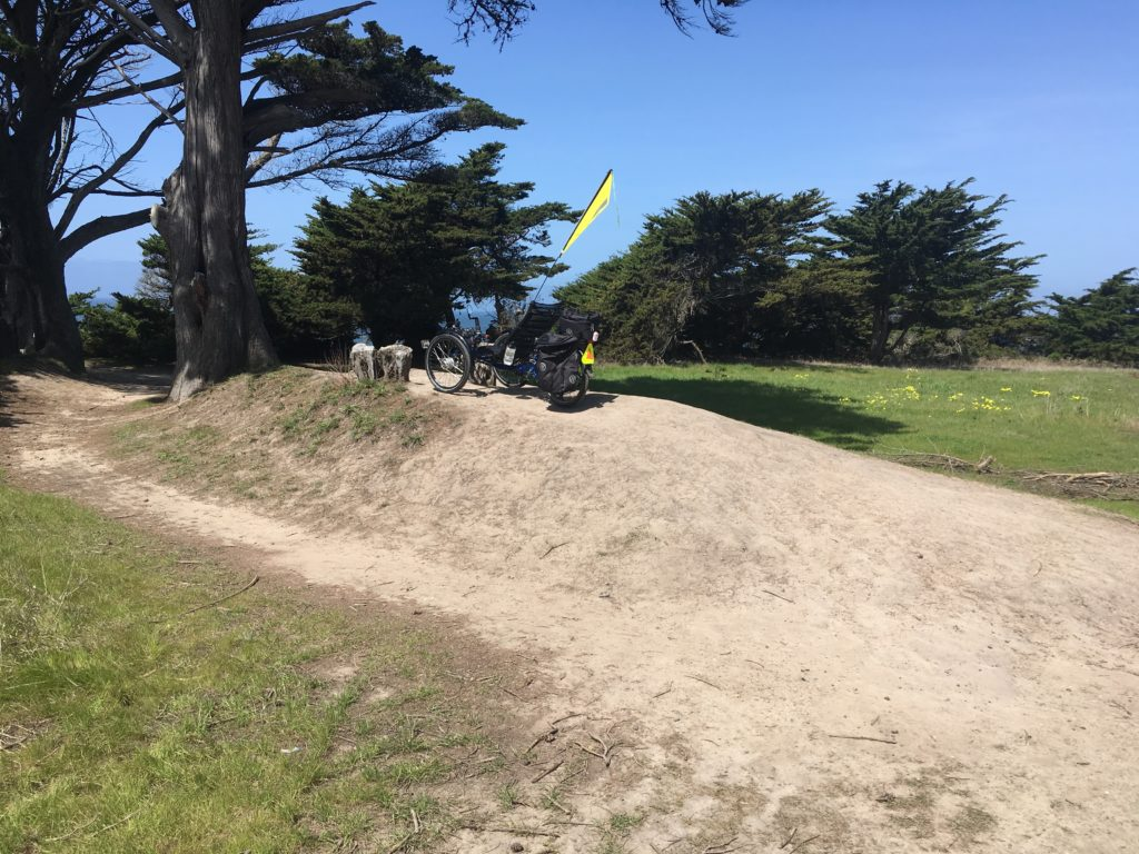 a recumbent trike on top of a small mound of dirt
