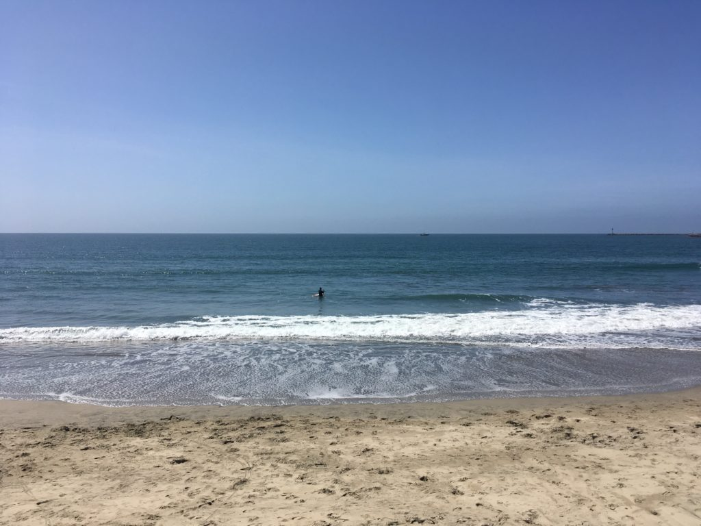 a surfer wades out to the surf with his surfboard