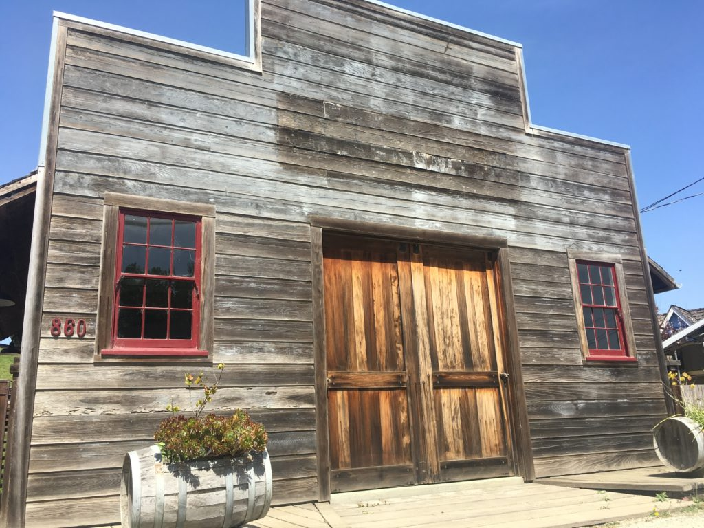 """an old wooden building with a false front and big front doors. The word """"blacksmith"""" is barely discernable."""