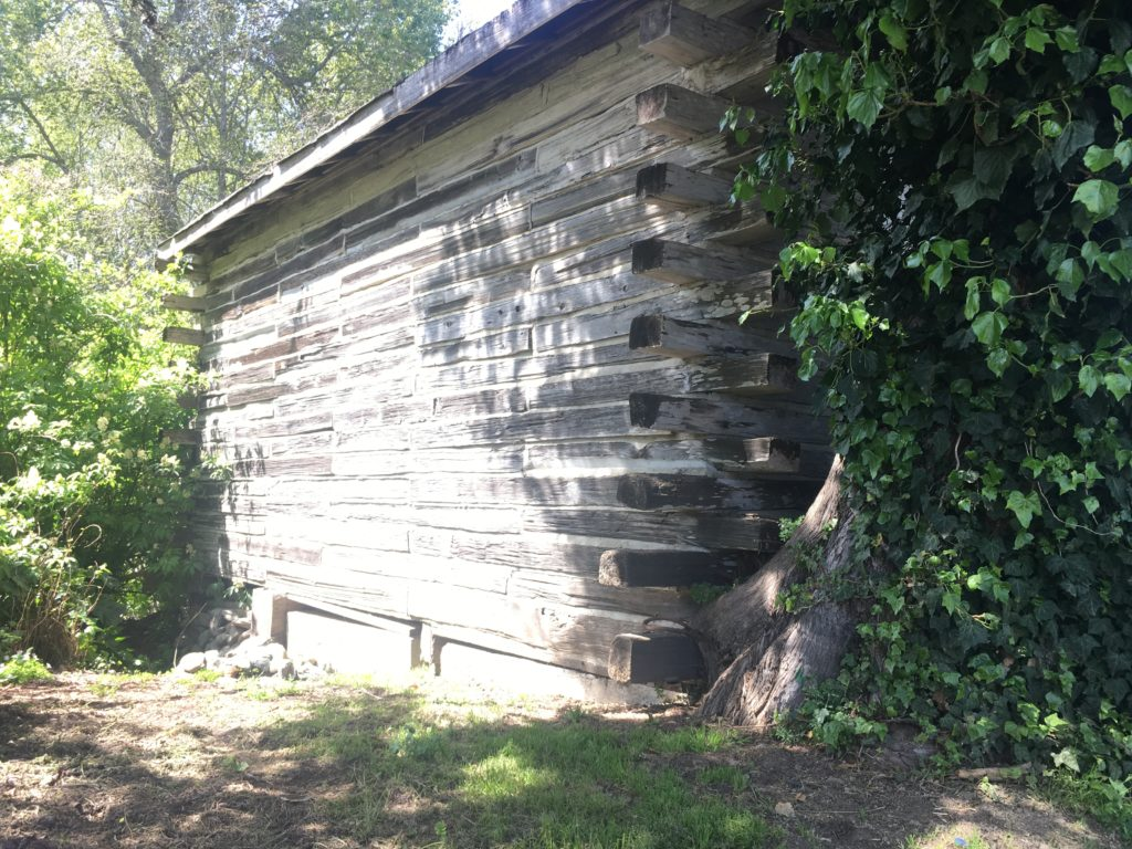 a side of a log building that may be very old