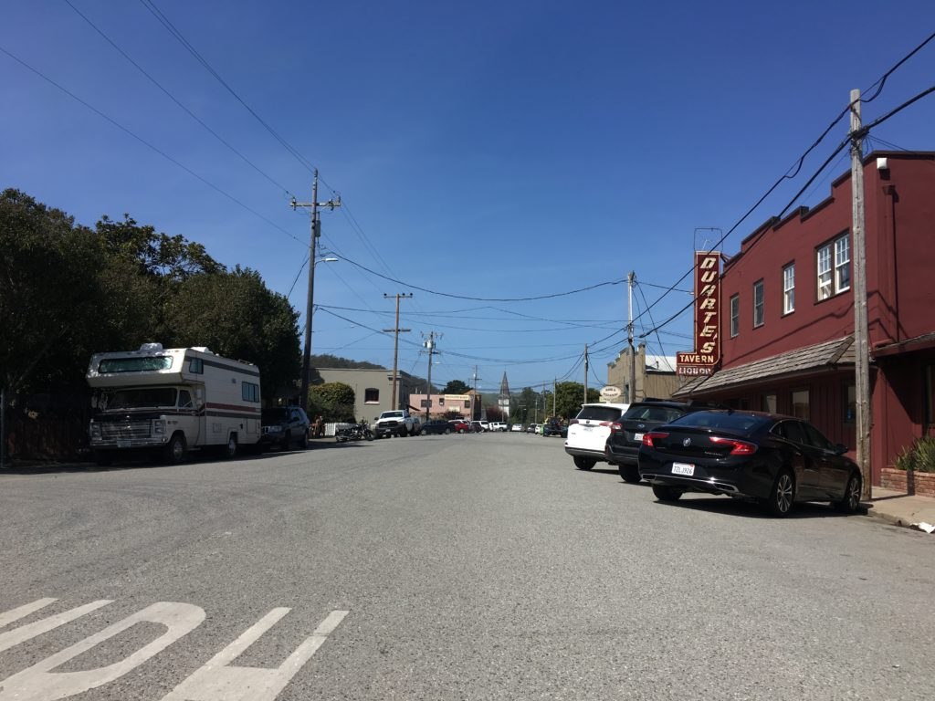 A main street of a small town, with buildings on either side and cars parked along the street.