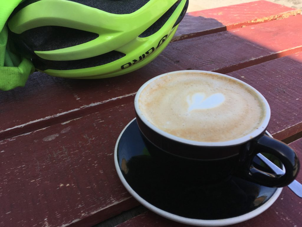 a wooden table with a cup of coffee and saucer, and a bicycle helmet.