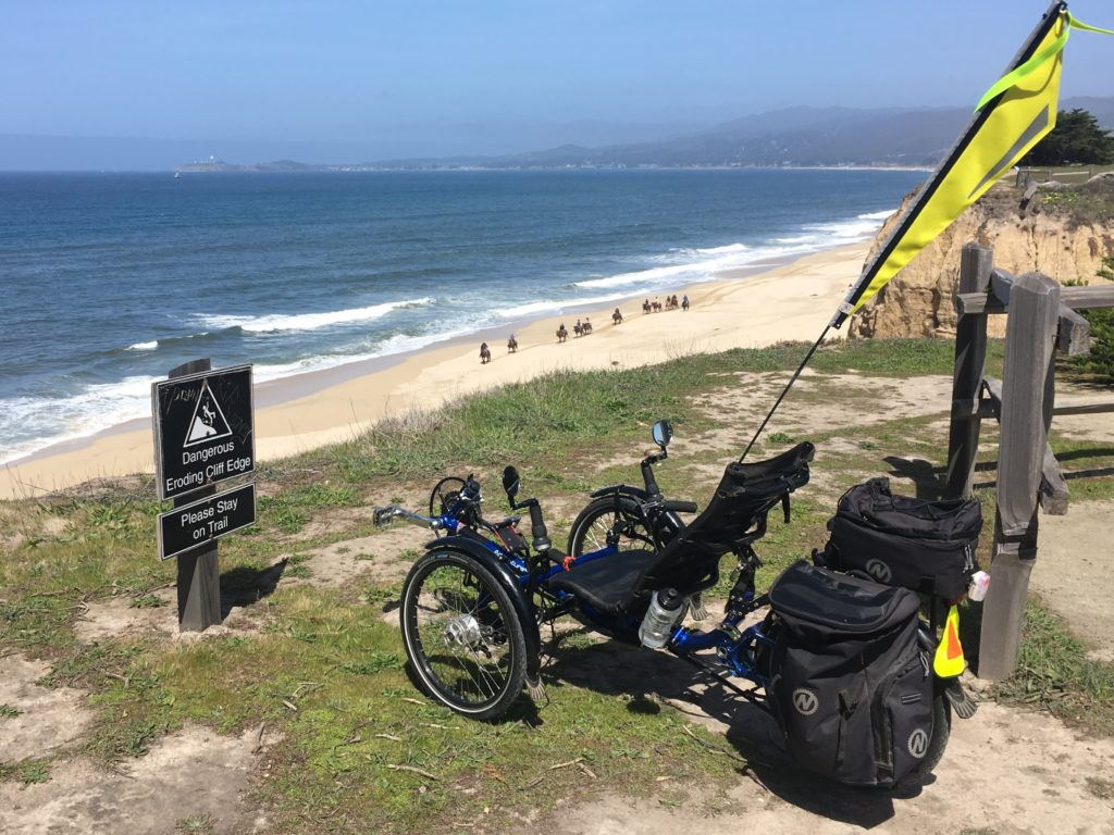 "a recumbent trike parked near a sign that says ""stay away - unstable cliffs"". Down below the bluff is a sandy beach with people riding horses"